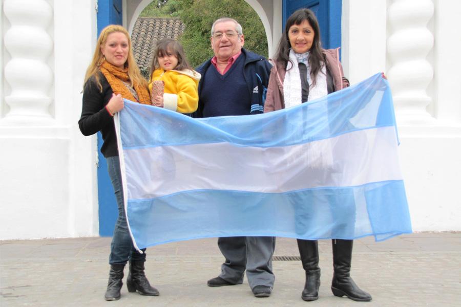 Imagen ilustrativa de una familia sosteniendo una bandera argentina en el Congreso de Tucumán