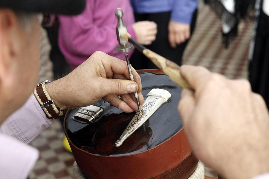 Imagen ilustrativa de un hombre tallando un cuchillo.