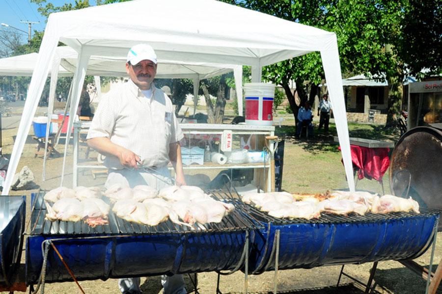 Fotografía ilustrativa de un señor vendiendo pollos a la parrilla.