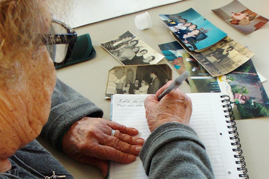 Imagen ilustrativa de una adulta mayor escribiendo.