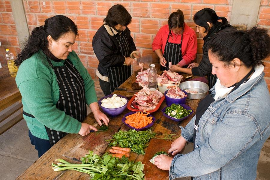 Fotografía de personas preparando una ensalada.