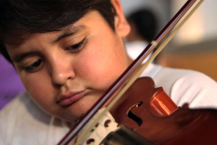 Fotografía ilustrativa de un chico tocando el violín.