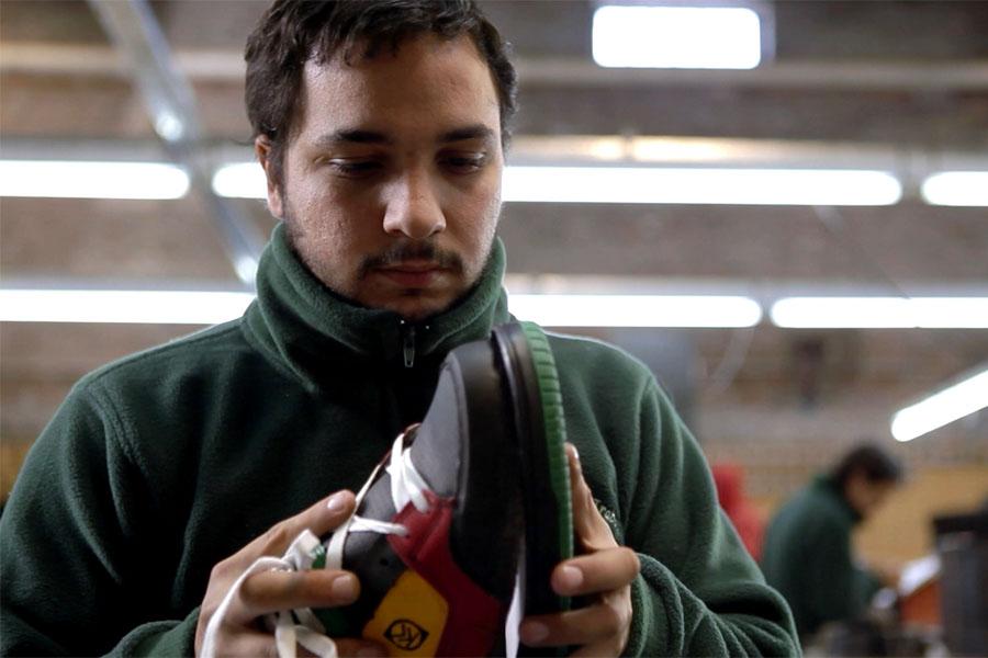 Fotografía ilustrativa de un hombre pegando un zapato.